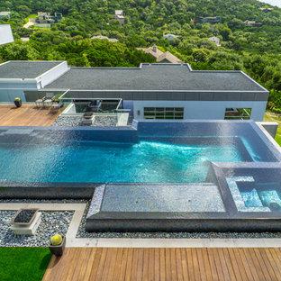 Immagine di una grande piscina a sfioro infinito minimalista personalizzata in cortile con fontane e pedane