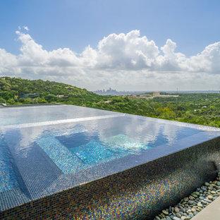 Idee per una grande piscina a sfioro infinito minimalista personalizzata in cortile con fontane e pedane
