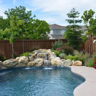 Ispirazione per una piscina naturale stile shabby personalizzata di medie dimensioni e dietro casa con fontane e pavimentazioni in pietra naturale