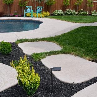 Ejemplo de piscina con fuente natural, romántica, de tamaño medio, a medida, en patio trasero, con adoquines de piedra natural