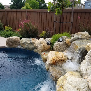 Medium sized vintage back custom shaped natural swimming pool in Sacramento with a water feature and natural stone paving.