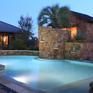 Inspiration for a large country backyard custom-shaped natural pool in Austin with a pool house and concrete pavers.
