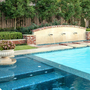 Example of a large classic backyard stone and custom-shaped pool fountain design in Houston
