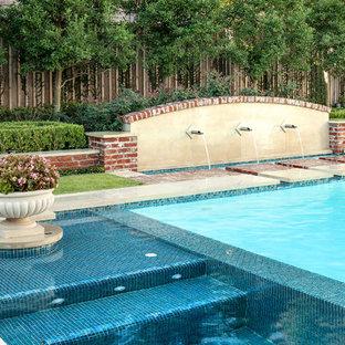 Immagine di una grande piscina classica personalizzata dietro casa con fontane e pavimentazioni in pietra naturale
