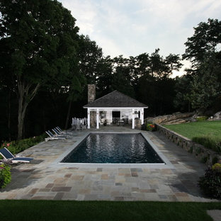 Pool house - traditional stone and rectangular pool house idea in New York