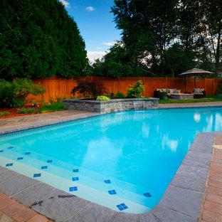 Diseño de piscina con fuente asiática, de tamaño medio, en forma de L, en patio trasero, con adoquines de hormigón