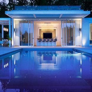 Ejemplo de casa de la piscina y piscina alargada, actual, de tamaño medio, rectangular, en patio trasero, con adoquines de hormigón