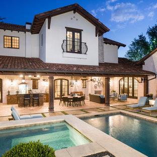 """Ispirazione per una grande piscina mediterranea a """"L"""" in cortile con una vasca idromassaggio e lastre di cemento"""