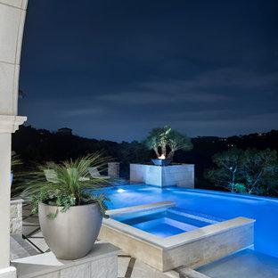 Foto de piscinas y jacuzzis infinitos, tradicionales renovados, extra grandes, a medida, en patio trasero, con suelo de baldosas