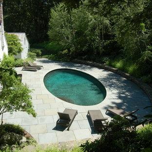Foto de piscina clásica, de tamaño medio, redondeada, en patio trasero, con adoquines de piedra natural