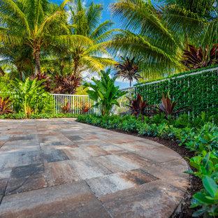 Foto de piscina tropical, de tamaño medio, a medida, con adoquines de hormigón