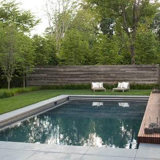Diseño de piscina con fuente alargada, de estilo de casa de campo, de tamaño medio, rectangular, en patio trasero, con losas de hormigón