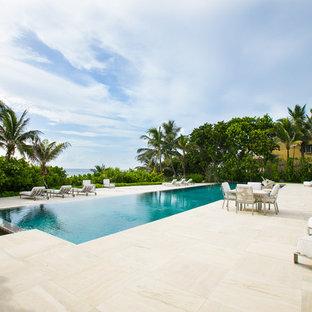 Huge trendy backyard stone and rectangular infinity pool photo in Miami