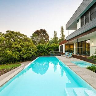 Foto de piscina alargada, moderna, grande, rectangular, en patio delantero, con adoquines de piedra natural