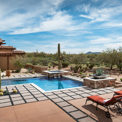 Example of a large southwest backyard concrete paver and l-shaped lap hot tub design in Phoenix