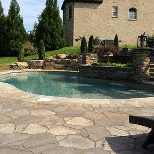 Esempio di una grande piscina naturale chic personalizzata dietro casa con fontane e pavimentazioni in mattoni