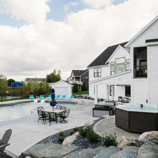 Imagen de piscinas y jacuzzis alargados, tradicionales renovados, grandes, a medida, en patio trasero, con losas de hormigón