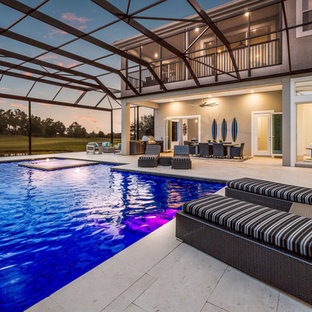 This is an example of a large modern backyard rectangular pool in Tampa with with privacy feature.