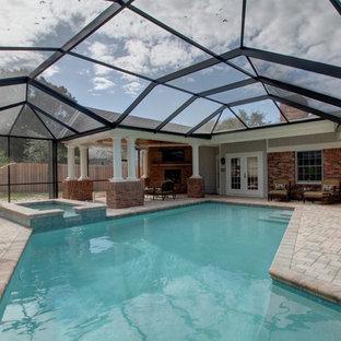 Imagen de piscinas y jacuzzis alargados, tradicionales, grandes, en forma de L, en patio trasero, con adoquines de ladrillo
