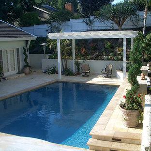 """Immagine di una piscina monocorsia stile shabby a """"L"""" di medie dimensioni e dietro casa con fontane e piastrelle"""