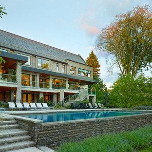 Modelo de piscina con fuente elevada, contemporánea, grande, rectangular, en patio trasero, con adoquines de ladrillo