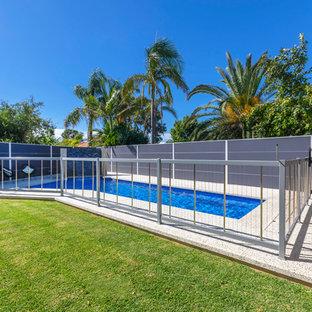 Ejemplo de piscina con fuente alargada, contemporánea, grande, a medida, en patio trasero, con granito descompuesto