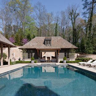 Aménagement d'un grand couloir de nage arrière classique rectangle avec un bain bouillonnant et des pavés en pierre naturelle.