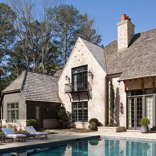 Ejemplo de piscinas y jacuzzis alargados, tradicionales renovados, grandes, rectangulares, en patio trasero, con adoquines de piedra natural