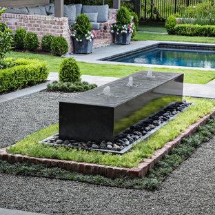 Foto de piscina con fuente infinita, tradicional renovada, de tamaño medio, rectangular, en patio, con adoquines de piedra natural