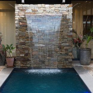 Immagine di una piscina contemporanea rettangolare di medie dimensioni e in cortile con fontane e pedane