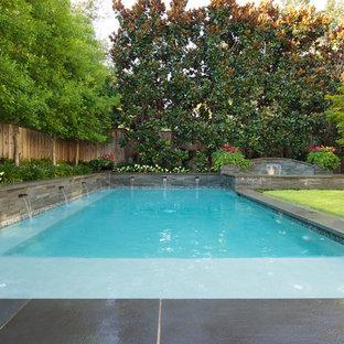 Ispirazione per una grande piscina a sfioro infinito tradizionale rettangolare dietro casa con fontane e pavimentazioni in pietra naturale