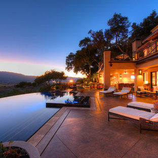 Photo of an expansive country courtyard custom-shaped infinity pool in San Francisco with a water feature and stamped concrete.