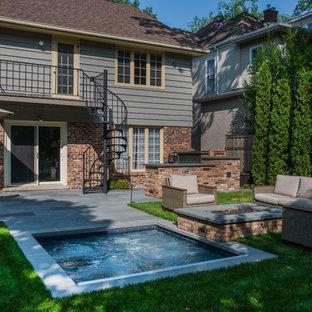 Esempio di una piccola piscina tradizionale rettangolare dietro casa con una vasca idromassaggio e pavimentazioni in pietra naturale