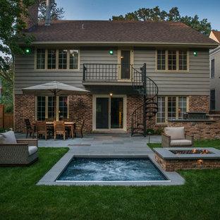 Immagine di una piccola piscina tradizionale rettangolare dietro casa con una vasca idromassaggio e pavimentazioni in pietra naturale
