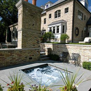 Foto di una piccola piscina classica rettangolare dietro casa con una vasca idromassaggio e pavimentazioni in pietra naturale