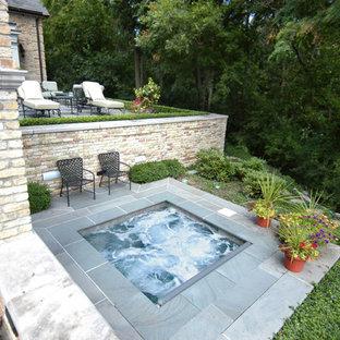 Immagine di una piccola piscina classica rettangolare dietro casa con una vasca idromassaggio e pavimentazioni in pietra naturale