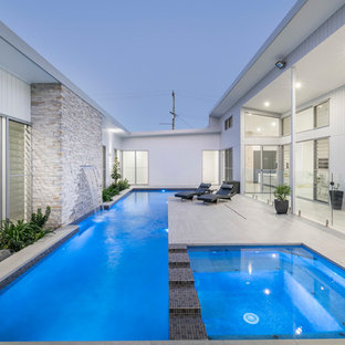 Photo of a contemporary courtyard rectangular lap pool in Brisbane with a hot tub.