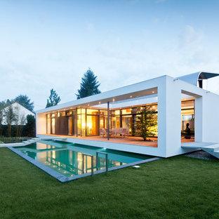 Imagen de piscina alargada, actual, grande, rectangular, en patio lateral, con losas de hormigón