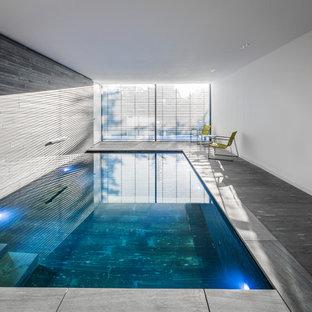 Imagen de piscina alargada, moderna, grande, interior y en forma de L, con adoquines de piedra natural