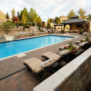 Imagen de piscina con tobogán alargada, clásica renovada, grande, rectangular, en patio trasero