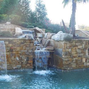 Foto de piscina con tobogán rural, grande, a medida, en patio trasero, con adoquines de piedra natural
