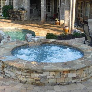 Diseño de piscina con tobogán rústica, grande, a medida, en patio trasero, con adoquines de piedra natural