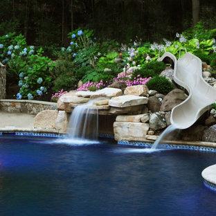 Ejemplo de piscina con tobogán alargada, clásica, grande, a medida, en patio trasero, con gravilla