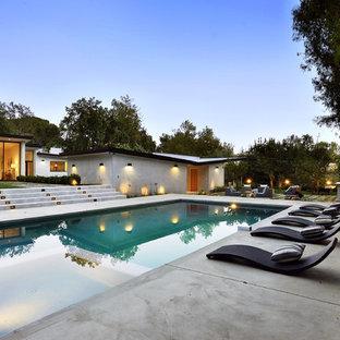Modelo de piscinas y jacuzzis alargados, modernos, grandes, rectangulares, en patio trasero, con losas de hormigón