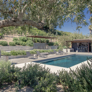 Ejemplo de casa de la piscina y piscina contemporánea, rectangular, en patio trasero, con entablado