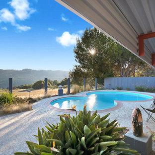 Ejemplo de piscina vintage, a medida, en patio trasero, con granito descompuesto