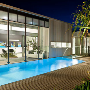 Photo of a contemporary back custom shaped lengths swimming pool in Brisbane with decking and a water feature.