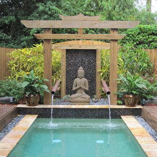 Ejemplo de piscina con fuente de estilo zen, rectangular, con entablado