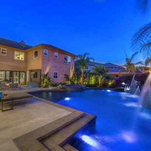 Modelo de piscina con fuente natural, tropical, grande, a medida, en patio trasero, con adoquines de hormigón