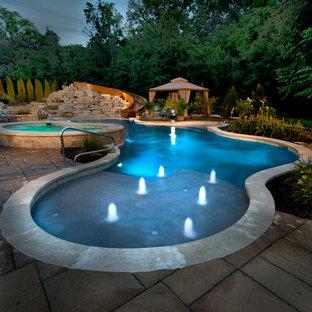 Modelo de piscinas y jacuzzis naturales, tradicionales, de tamaño medio, a medida, en patio trasero, con adoquines de hormigón